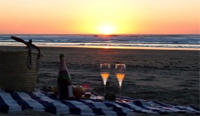 Sunset beach picnic with a bottle or wine or sparkling